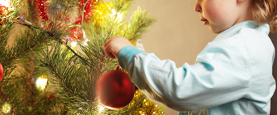 boy hangs Christmas toy