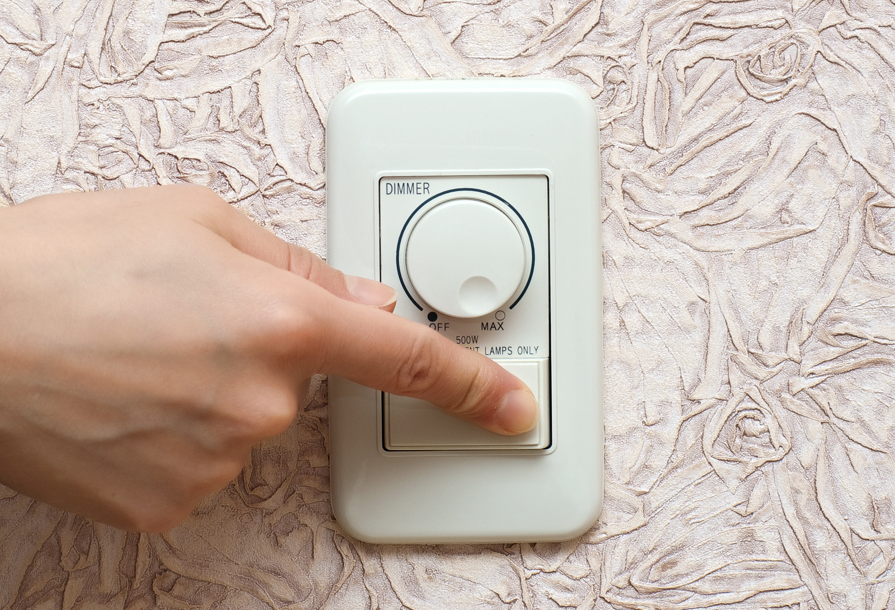 Women's hand switches off light in the room